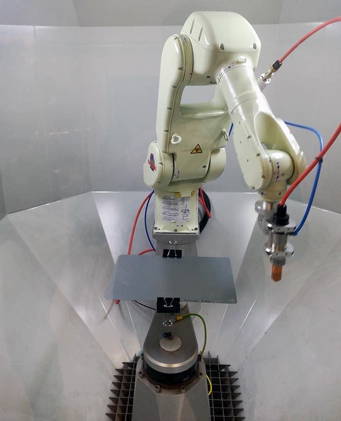 Abbildung 1: Das robotergetriebene plasmabrush PB3-System mit fixiertem Stahlblech ist betriebsbereit. um die Haftung von Haftklebstoffen auf Haushaltswaren zu verbessern.
